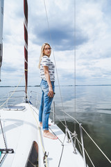 Slender barefoot blonde is standing on white yacht