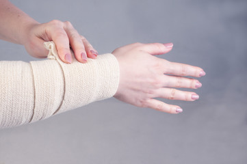 Fractures and dislocations concept. Female hand in a white bandage. A useful preparation for the painful palm of a person's hand.