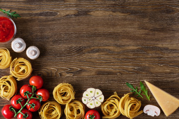 Ingredients for tagliatelle pasta on a wooden background.
