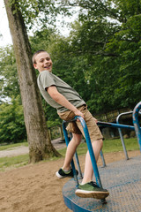a young boy playing and spinning on a merry-go-round