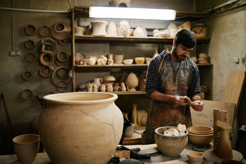 Talented artisan looking at beautiful ceramics on work table in