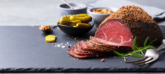 Roasted beef, pastrami on slate cutting board. Copy space