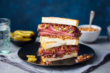 Roast beef sandwich on a plate with pickles. Copy space.