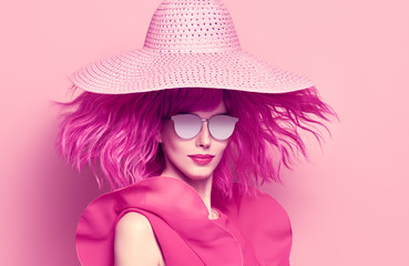 Fashion Portrait girl with Pink Hair in Hat, Trendy Sunglasses. Young woman in Stylish Outfit. Glamour Beautiful Model on Pink. Spring Summer Lady. Art Luxury fashion Style