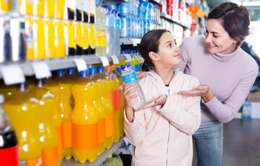 woman with daughter choosing refreshing beverages in supermarket