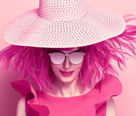 Glamour Beautiful Lady Smiling. Party fashionable Hairstyle. Fashion woman in pink Summer Dress. Young Playful female model in Stylish fashion Hat. Trendy Sunglasses