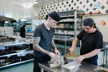 Chef and  cook apprentice working together in a catering kitchen