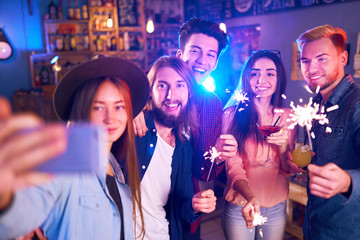 Selfie Time.Young Group of Friends Partying In A Nightclub And Toasting Drinks. Happy Young People With Sparklers At Pub. The People Have A Great Mood And They Smile A Lot.