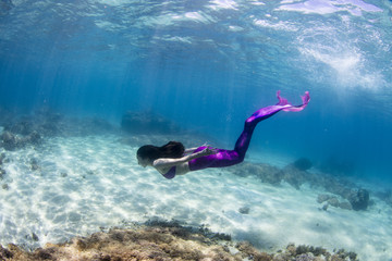 Female mermaid swimming underwater