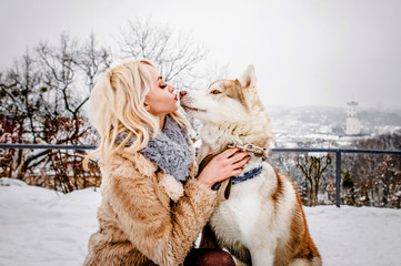 A beautiful blonde hugs her dog in a winter park