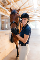 young woman rider in the barn smiling with her horse