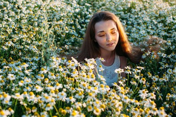 Emotional portrait of pretty young female in camomile field with sunbeam on her face