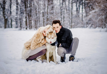 A pretty couple walks with their dog in a snowy park