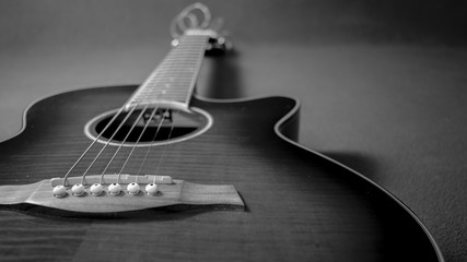 Retrato de una hermosa guitarra electroacústica situada a la izquierda de la imagen, mostrando el puente, la boca, el cuello y sus cuerdas
