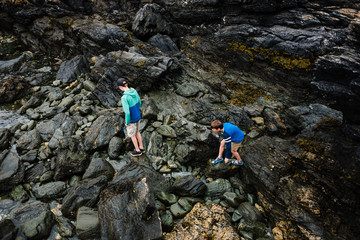 kids catching crabs in a  cove by the sea