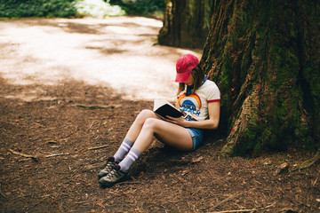 Woman reading a book sitting near a big sequoia tree.