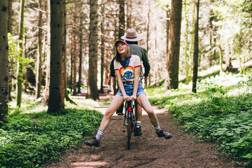 Young couple riding a bike on the woods.