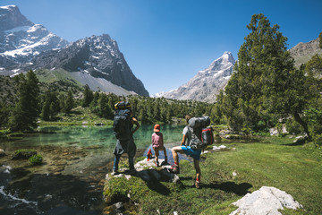 family with mountaineering and camping equipment standing in front of crystal clear lake in alpine mountain landscape