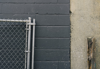 Chain-link fence leaning against building wall
