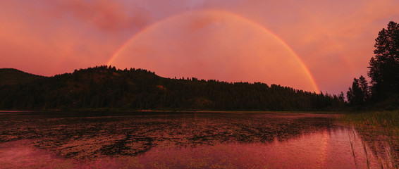 A rainbow and a dramatic sunset over a mountain lake