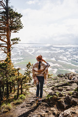 Boho woman wearing hat and poncho standing by the mountain. Cold weather, snow on hills. Winter hiking. Wanderlust.