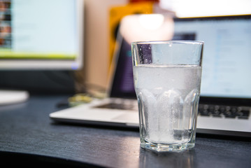 glass of water with aspirin. laptop on background. overloaded with office work
