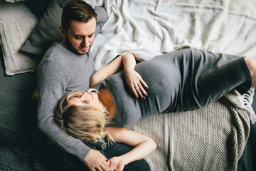 Pregnant couple cuddling on bed