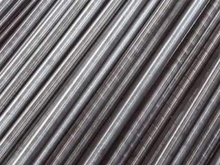 Steel pipes and rods laid parallel to the diagonal. Industrial abstract background.