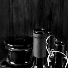 Different dark glass bottles for alcoholic drinks on black wooden background. Black and white photo