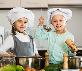 Two girls preparing vegetables and smiling indoors
