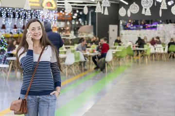 Young woman walking in the shopping center and talking on a white smartphone. Girl with long hair