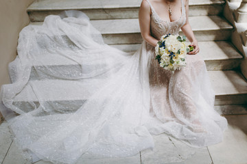 Beautiful wedding celebration. The bride in elegant ivory lace wedding dress with a necklace and a bouquet of peonies and blue berries sits on stone steps spreading skirt. Wedding wear, accessories