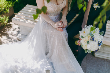 Beautiful wedding celebration. Bride in beautiful elegant lace wedding dress and bridegroom in black suit with bouquet of bride sitting on bench and holding hands outdoors. Wedding wear, accessories