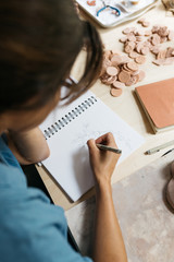 young woman working on concepts and sketching for small business ceramics diy making in home studio workshop