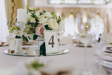 Beautiful decoration of a wedding banquet in a restaurant in pastel colors. Decoration of banquet dinner table vase with flower arrangement, candlestick, card with number of table in frame