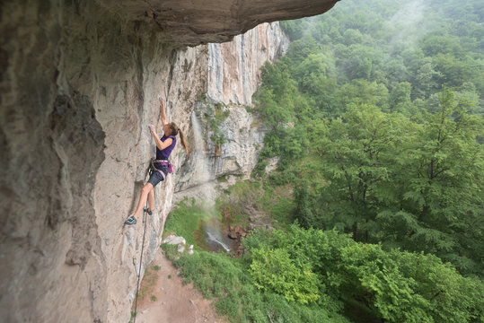 Side view of female rock climber ascending on rock wall