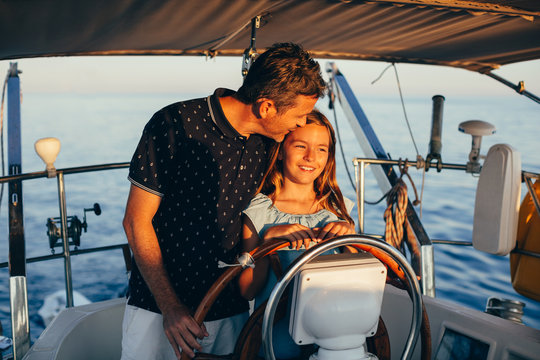 Father and daughter enjoying on a sailboat at sunset.