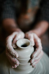 Closeup of potters hands shaping clay vase