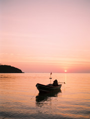 A boat moored on sea at sunset