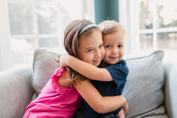 Brother and sister hugging on a big chair