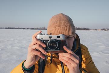 Photographer in yellow jacket taking photo on snowy winter field