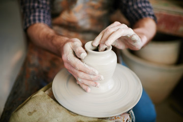 Skilled potters hands gently shaping clay vase on throwing wheel