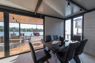 Luxury dining table with leather chairs in log cabin near river