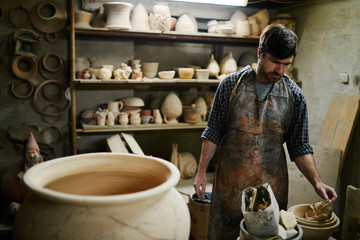 Talented artisan selling  beautiful ceramics in small pottery sh