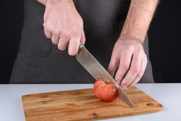A photo of the cooking process. A man cuts a tomato with a sharp knife.
