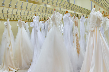 Stylish elegant wedding dress presented on hangers