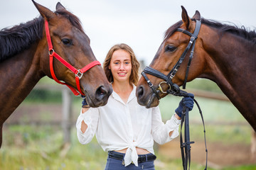 Young rider girl having fun with two her horses. Equestrian sport concept background