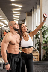 Beautiful athletic couple making selfie in gym after training