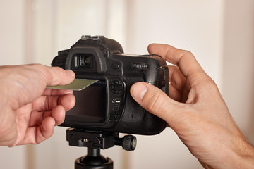 Closeup of male hand inserting bank card into camera, concept
