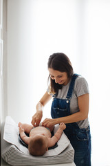 Portrait of a young mother giving baby a diaper change.